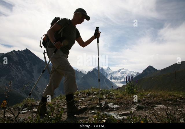 Trekker climbing up the mountain pass Karaturek in the Altai Mountains, Russia - Stock Image