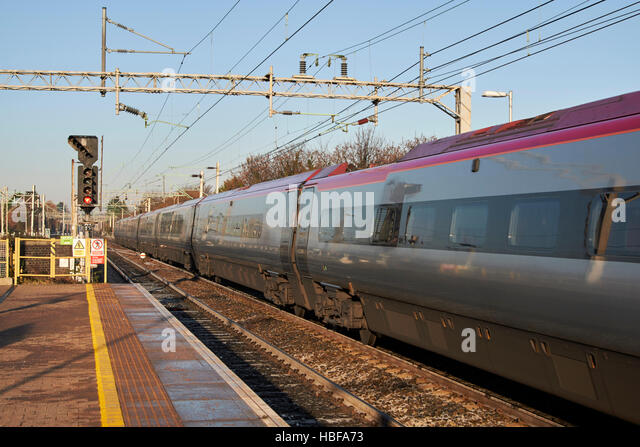 virgin trains intercity train speeding past overhead electricity wires on rail track at liverpool south parkway - Stock-Bilder
