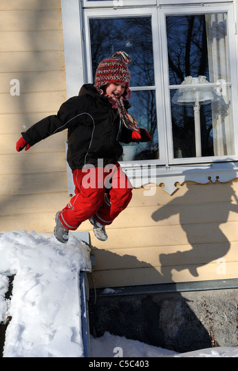 Low angle view of a little girl jumping in the snow - Stock Image