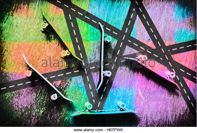 Unique colorful retro skateboard desks abstracted amongst a busy urban street background. Retro skaters parade - Stock Image