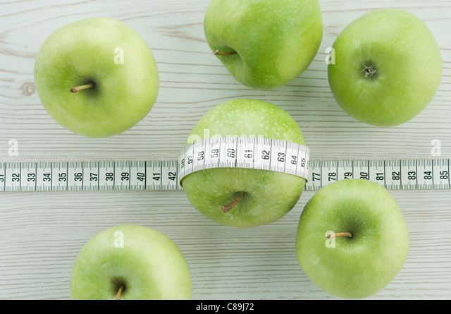 Green apple wrapped round with measuring tape - Stock Image