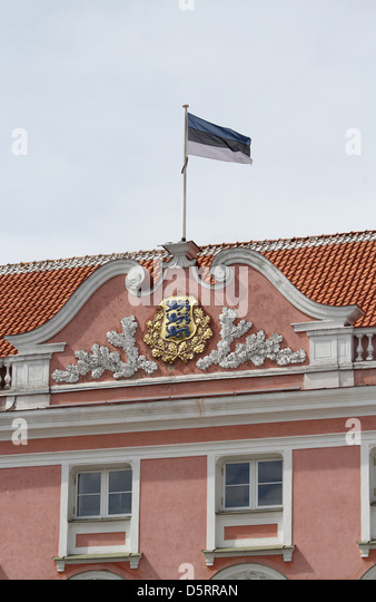 The front facade of the Estonian Parliament building with the national flag of Estonia flying - Stock Image