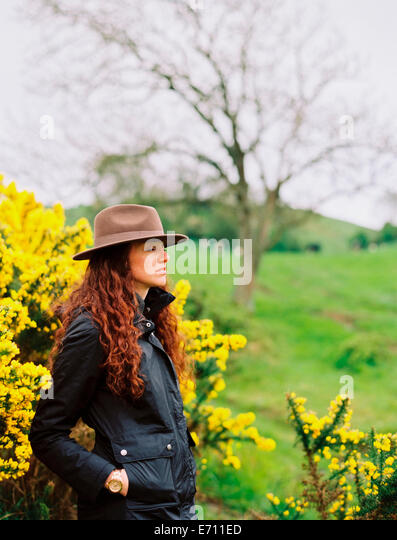 A woman with long curly hair wearing a hat, by a flowering gorse bush. - Stock Image