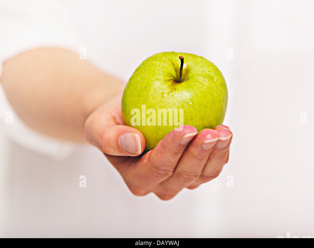 Woman's hand giving a green apple - Stock Image