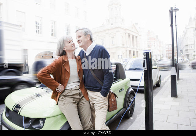 Couple charging electric car on street - Stock Image
