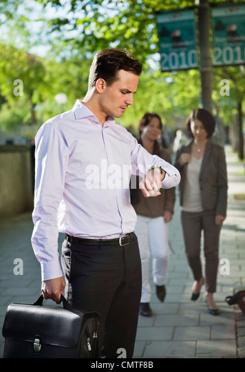 Man looking at watch with people in the background - Stock Image