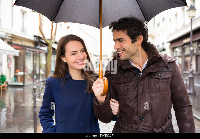 Happy smiling woman man umbrella shower - Stock-Bilder