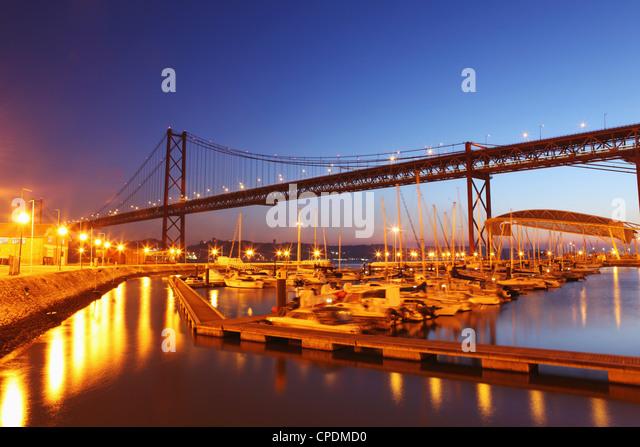 Boats on the River Tagus move at night in the Doca de Santa Amaro marina under the 25 April Bridge, Lisbon, Portugal, - Stock-Bilder