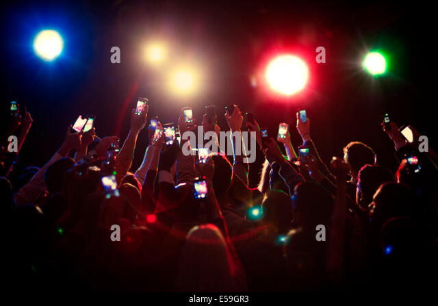 Audience using camera phones at concert - Stock Image