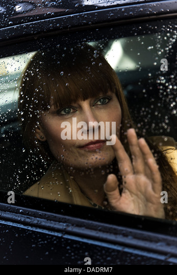 Woman waving and looking out of car window - Stock Image