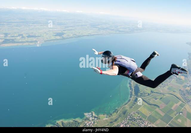 A woman making a fun skydive above lake Neuchatel in Switzerland - Stock Image
