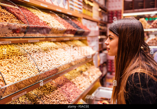 Young woman looking at foods in market, Istanbul, Turkey - Stock Image