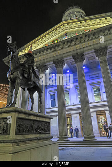 Glasgow buildings of the Merchant City,Scotland,UK at night - GOMA and traffic cone on head of Duke Of Wellington - Stock Image