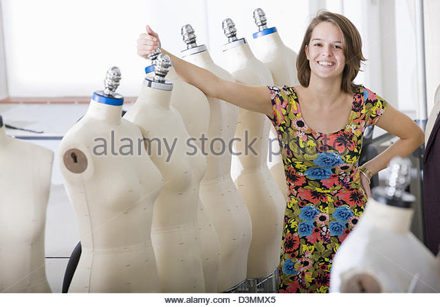 Fashion design student standing with  mannequins - Stock Image