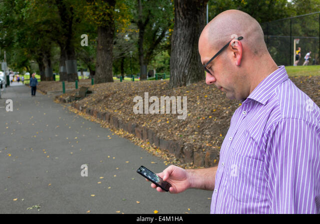 Melbourne Australia Victoria Flagstaff Gardens city park man smartphone checking messages texting - Stock Image