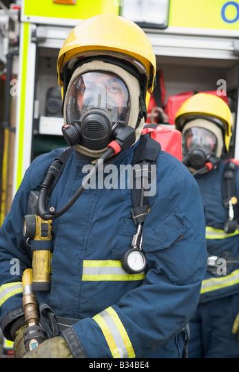 Two firemen in masks standing near fire engine (depth of field) - Stock Image