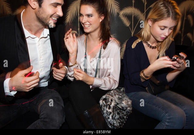Young adults socializing at night club - Stock Image
