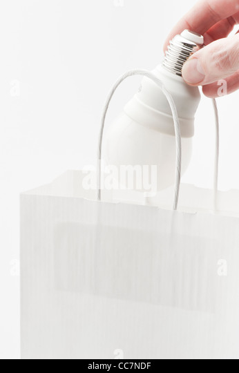 Hand placing energy efficient lightbulb in paper bag - Stock Image
