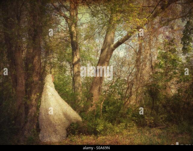 Hooded Woman in White in Woods - Stock Image