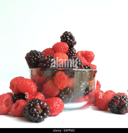 Glass bowl of raspberries and blackberries - Stock Image
