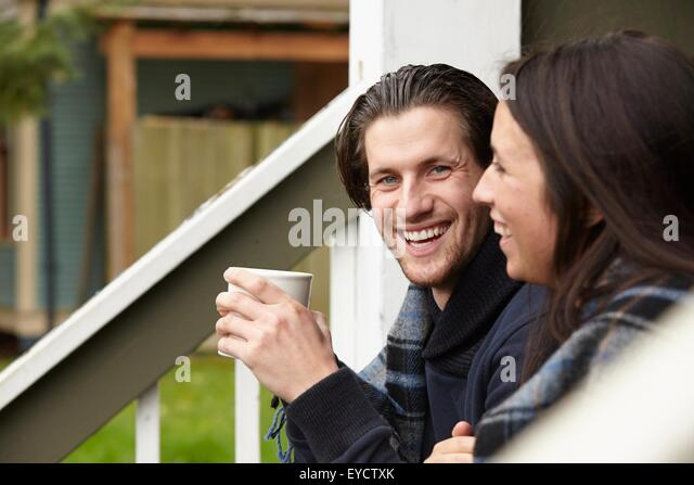 Young couple sitting on porch step drinking coffee - Stock Image