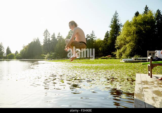 Man jumping into lake, Seattle, Washington, USA - Stock Image