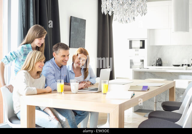 Happy family of four using laptop at home - Stock Image