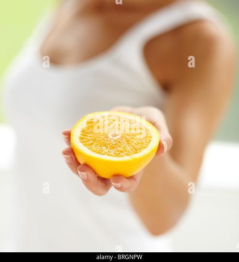 Woman holding orange fruit segment - Stock-Bilder