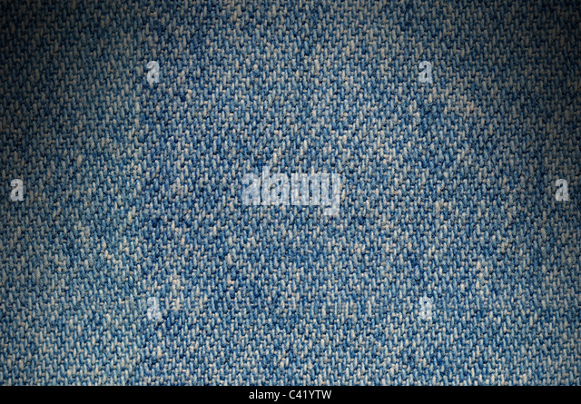 Blue denim fabric texture background lit dramatically from above - Stock Image