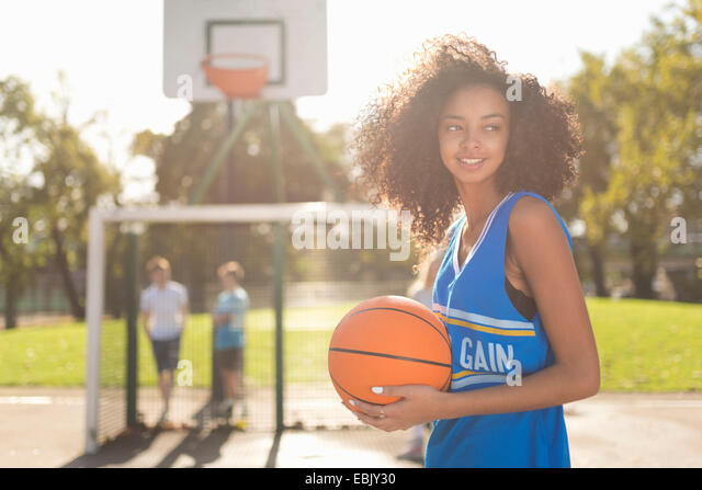 Smiling young female basketball player holding basketball - Stock Image