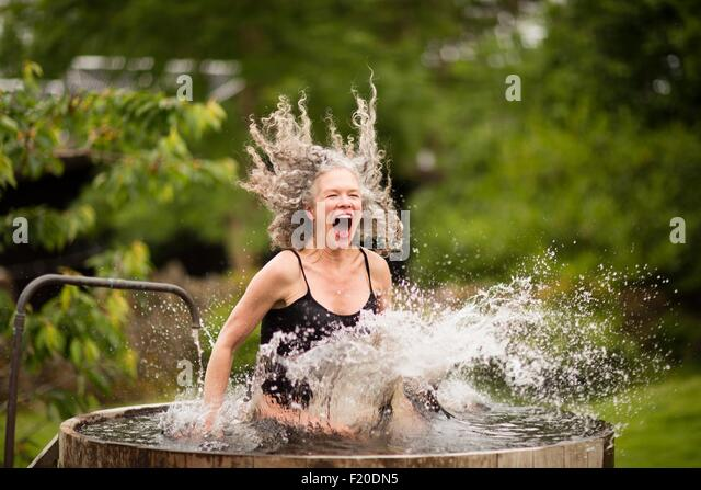 Mature woman splashing into fresh cold water tub at eco retreat - Stock Image