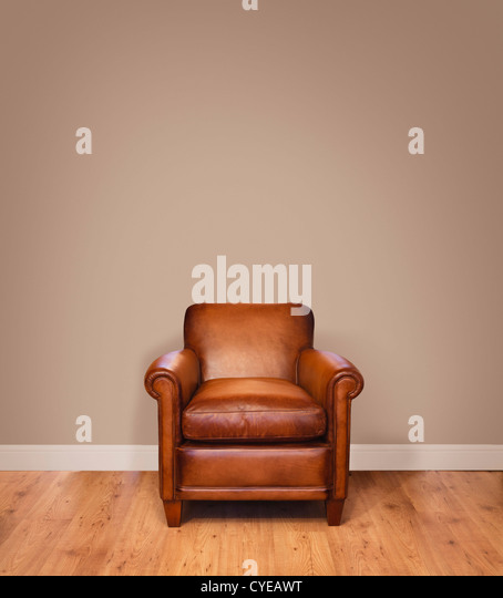 Leather armchair on a wooden floor against a plain background wall with lots of copyspace. The wall has a clipping - Stock Image