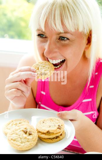 Woman eating biscuits - Stock-Bilder