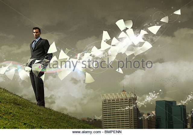 Paperwork flying around businessman and highrise buildings - Stock Image