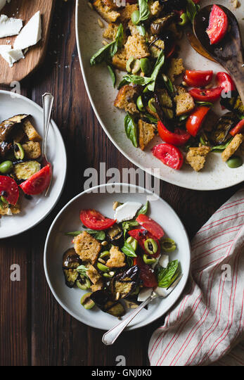 Roasted eggplant panzanella with capers, olives, and pine nuts, gluten-free. - Stock Image