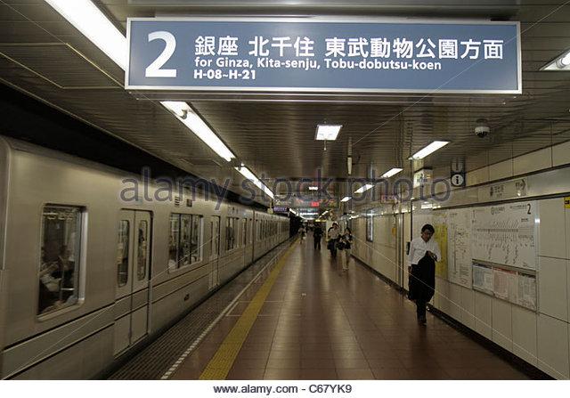 Japan Tokyo Hibiya Hibiya Line Station platform train Asian man - Stock Image