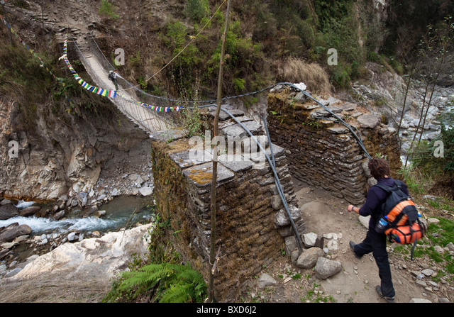 A male trekker approaches a footbridge while a female trekker pauses on the bridge ahead. - Stock Image