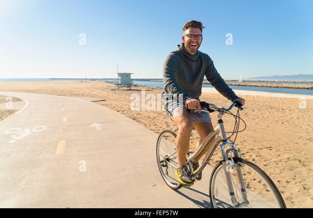 Young man cycling along pathway at beach - Stock Image