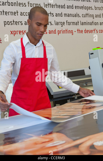 Industrial manual worker working in printing press - Stock Image