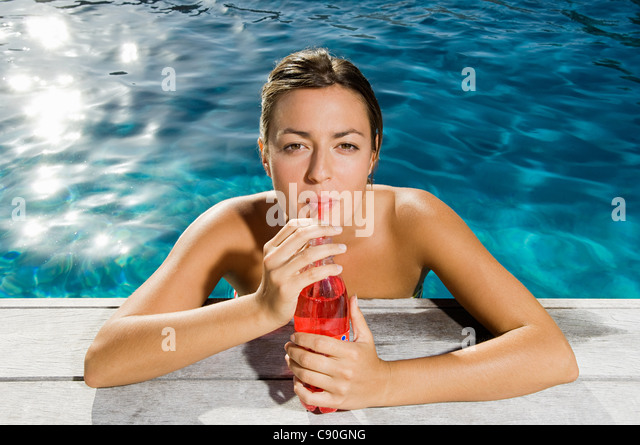 Young woman drinking soft drink at poolside - Stock Image