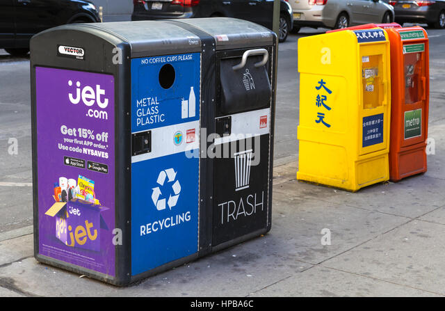 Solar-powered smart recycling and trash compactors deployed on a street in New York City. - Stock Image