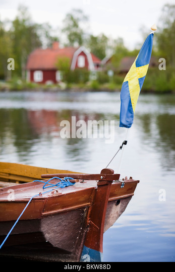 Boat, house and flag - Stock Image