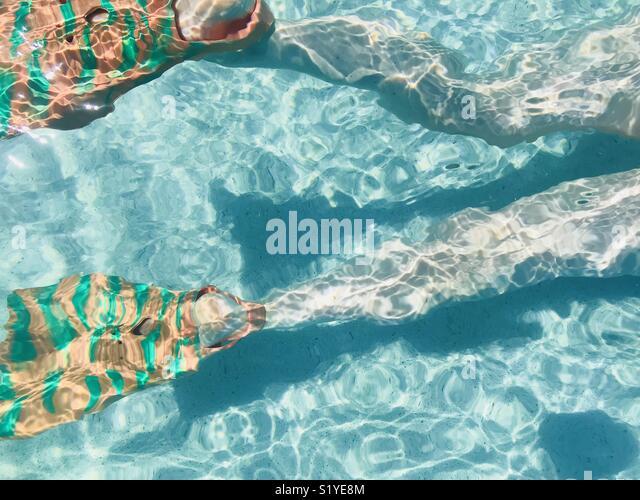 A woman swimming underwater. Fiji. - Stock Image