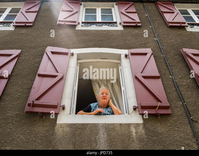 Old woman leaning out of open window, Laruns, Pyrénées-Atlantiques, France. - Stock Image