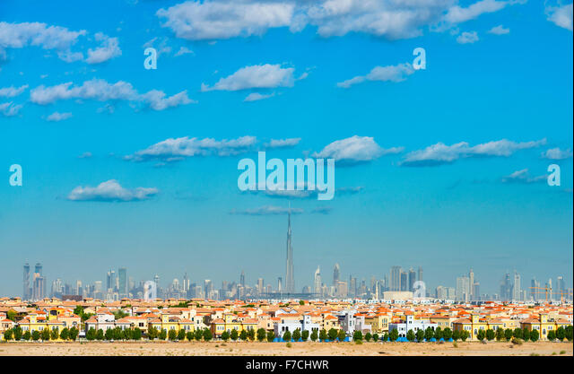 Skyline of Dubai with modern luxury villas at The Villa residential housing development in foreground in United - Stock Image