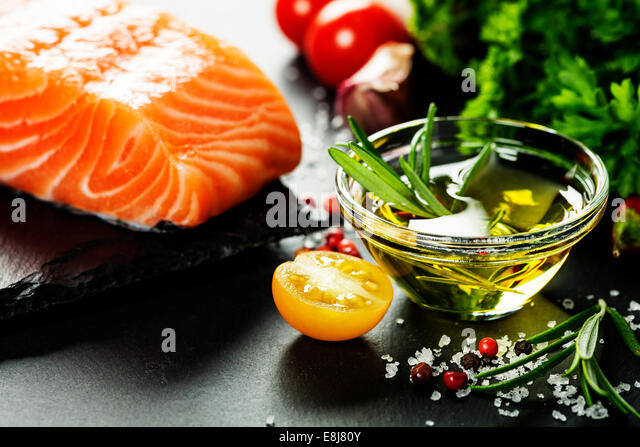 Delicious  portion of fresh salmon fillet  with aromatic herbs, spices and vegetables - healthy food, diet or cooking - Stock Image