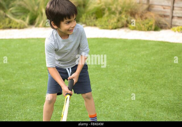 Front view of boy in garden playing cricket looking away smiling - Stock Image