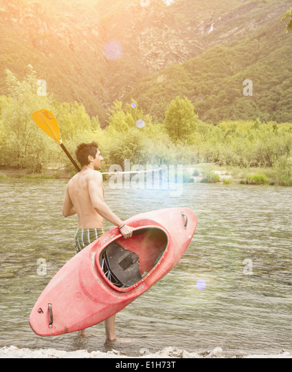 Young man with canoe on Toce riverbank, Piemonte, Italy - Stock Image