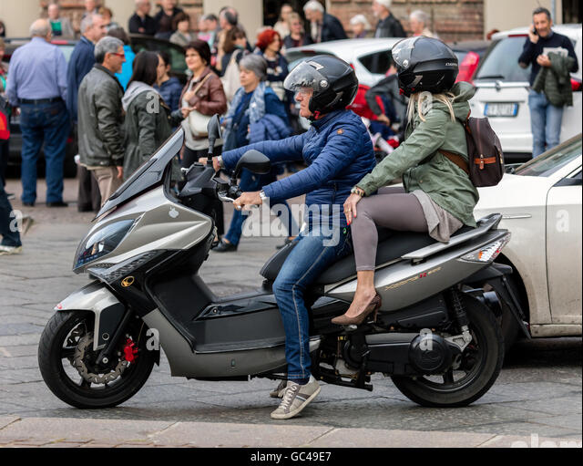 Middle-aged bike rider with his female passenger at the Piazza Castello in Turin, Italy - Stock Image