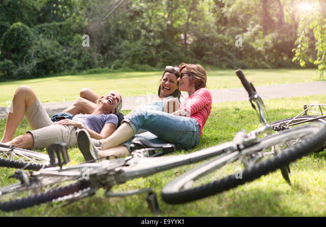 Three mature woman relaxing on grass after bicycle ride - Stock Image